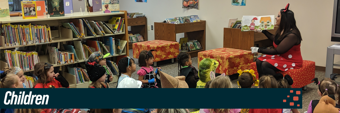 Children header image showing a group of kids during storytime being read to by woman dressed as minnie mouse