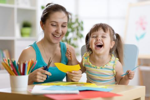 Mother and child work together on a craft as the child laughs out loud.